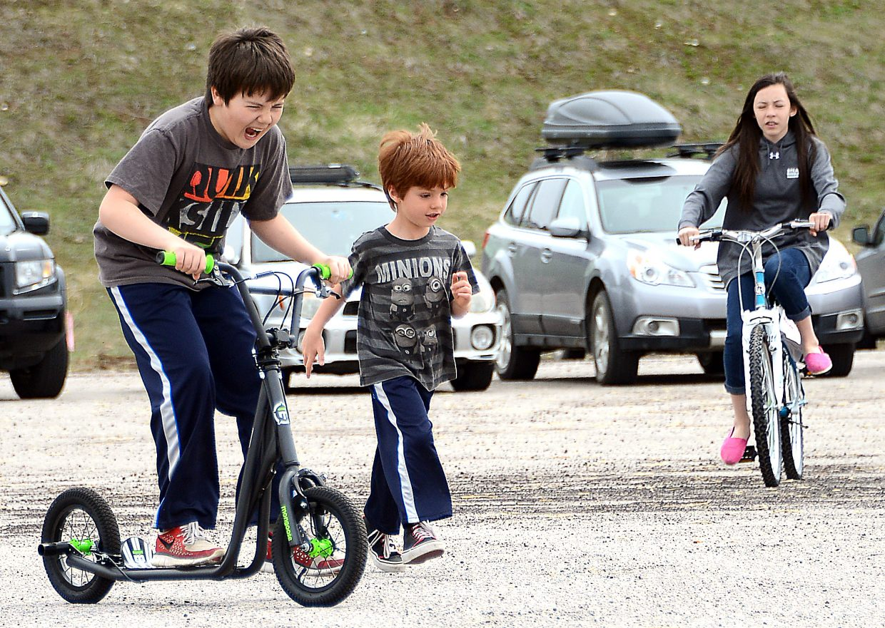 Andrew Terry, 11, rides his new scooter hard as younger brother, Bradley Snyder, 5, tries to keep up Saturday at the Easter Eggstravaganza at the Meadows parking lot in Steamboat Springs.
