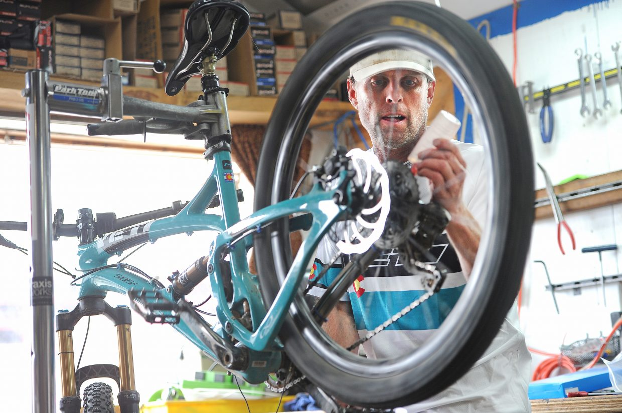 Chris Johns, owner of Wheels Bike Shop on Yampa Street, works on a bike in April 2016.
