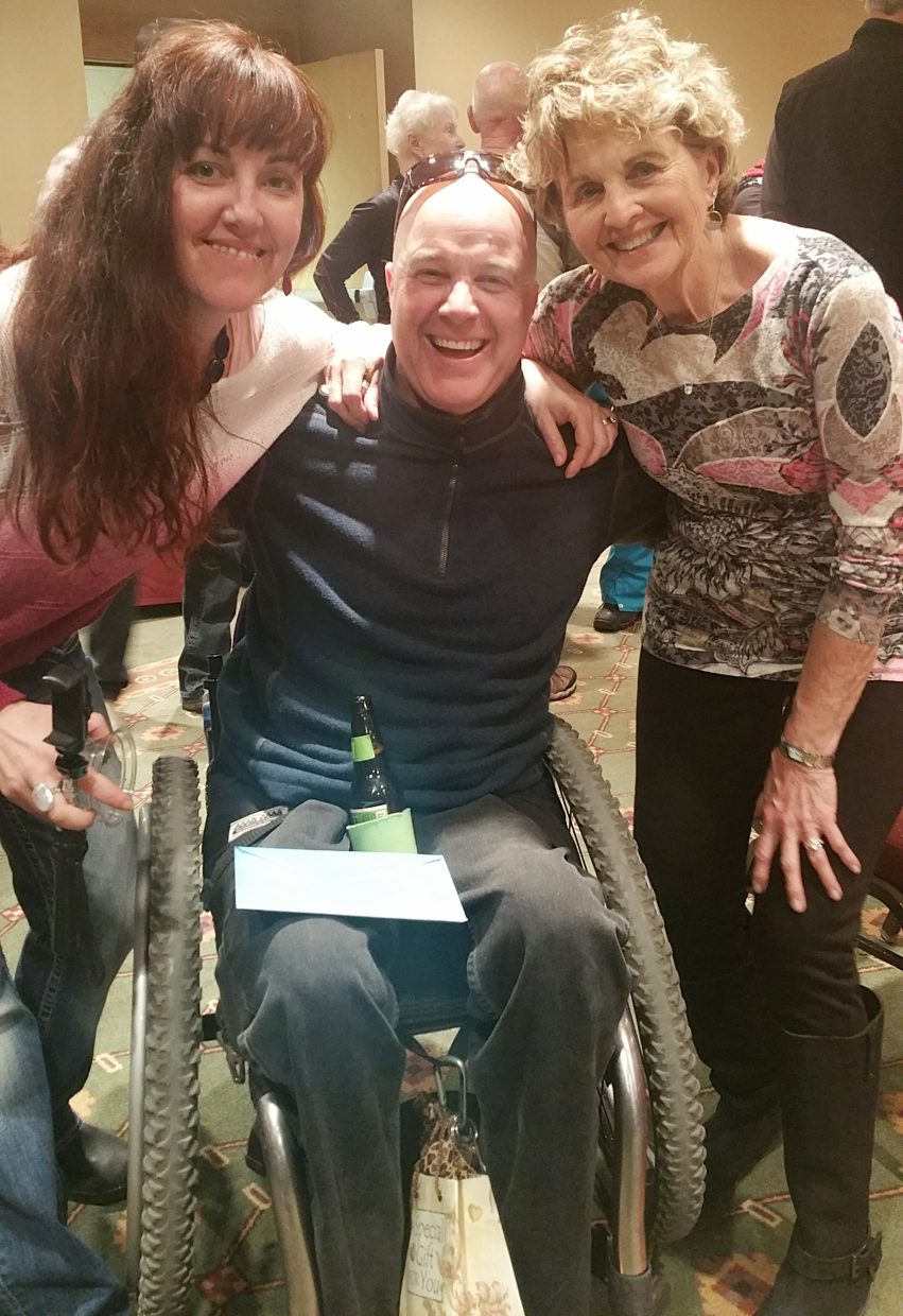 Craig Kennedy poses with his wife, Andrea Kennedy, left and his mother, Kathy Clarke, at a party to celebrate 20 years since a skiing injury that left him without the use of his legs.