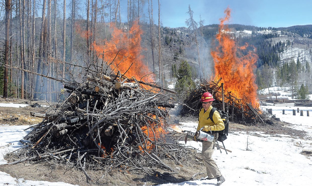 U.S. Forest Service zone fire management officer Sam Duerksen uses a drip torch to start several piles of slash material on fire Thursday morning in the Lynx Pass area. The controlled burn was part of a joint effort with a private landowner to clean up, create and access and to create a firebreak in an area known for wildfires. Duerksen said the cleanup will make fighting fires in the future easier and should make access in and out of the area safer in the case of a wildfire.