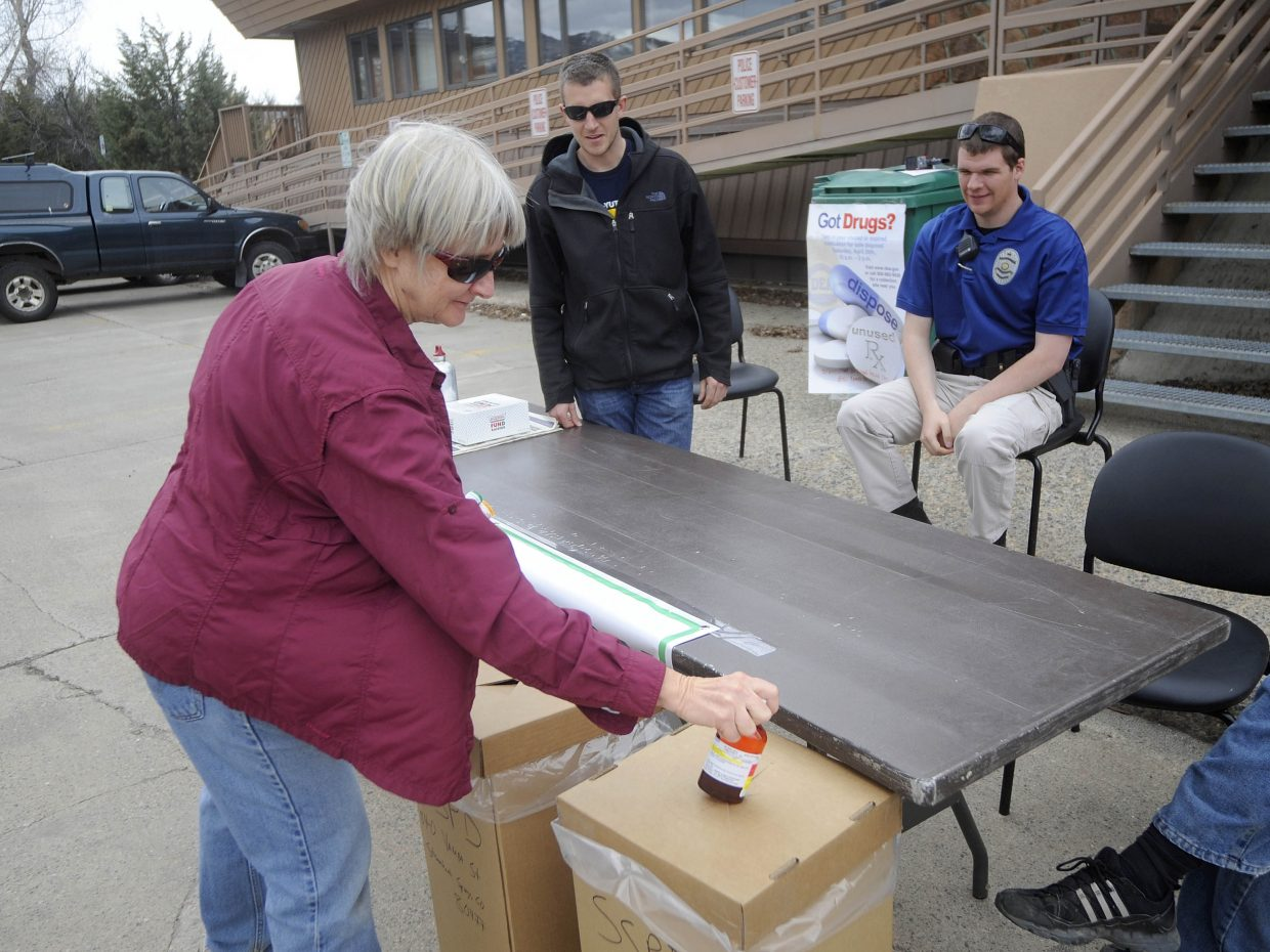 Pam Graham drops off medicines with Steamboat Springs Police Department officer Jeff Malchow, right, and records technician John Daschle during the National Prescription Drug Take Back Day held at the police department. Residents safely disposed of 92 pounds of drugs. Take Back Day also was held at the Oak Creek Town Hall.