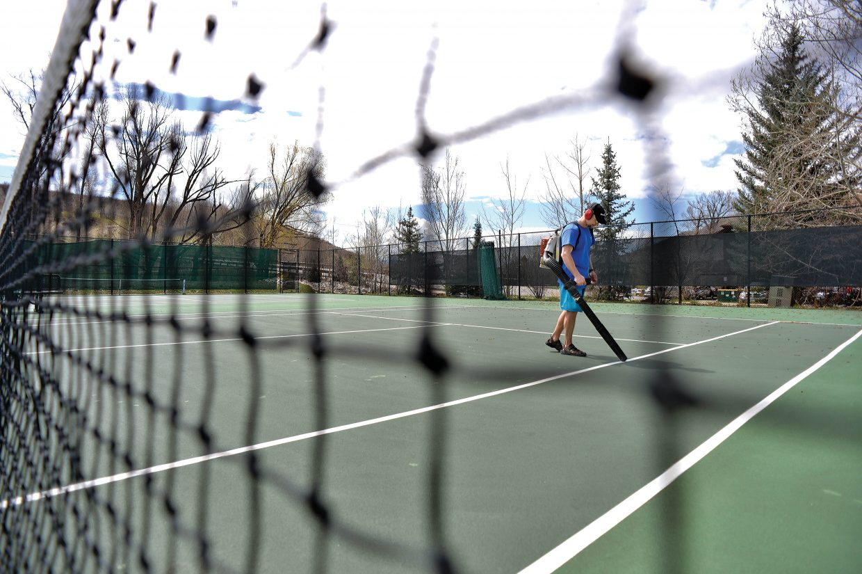 Old Town Hot Springs employee Lance O'Donnell uses a blower to clean the surface of the tennis courts Monday morning.