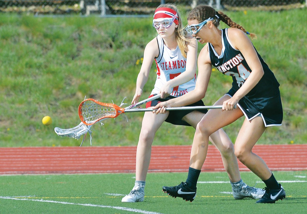 Steamboat Springs lacrosse player Libby Lukens and Grand Junction's Tyler Anderson battle during Monday night's game at Gardner Field. Despite Steamboat goal keeper Summer Dorr's 20 saves, the Sailors lost the game 17-0.