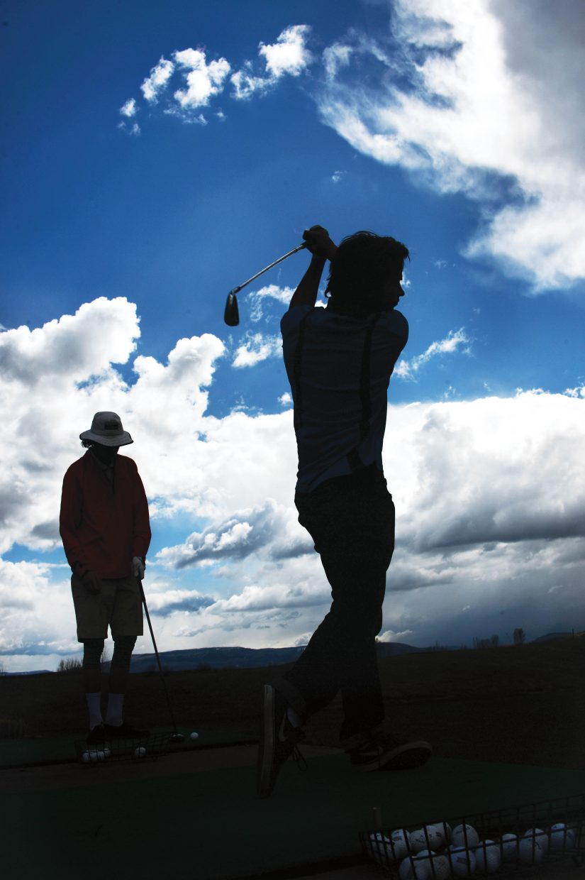 Spencer Petersen, front, and Andrew Firestone hit golf balls at the Haymaker driving range Monday afternoon. Right now, the practice facilities at the course are open, but on Thursday, golfers will be able to play all 18 holes. It's one of the earliest openings in the golf course's history.