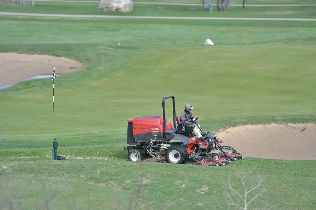 A groundskeeper mows the rough at the Rollingstone Ranch Golf Club Monday morning. The course opened all 18 holes for play Monday.