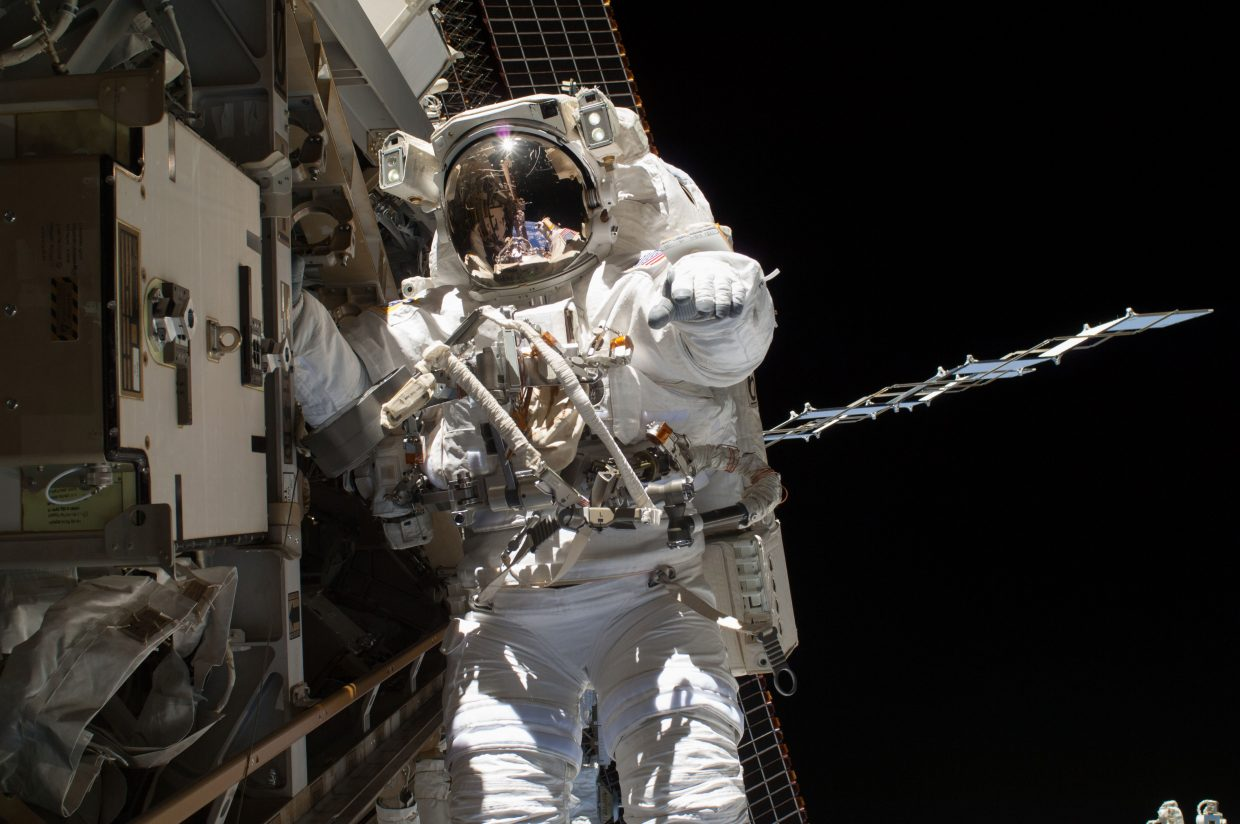 NASA astronaut Steve Swanson is pictured during a spacewalk to replace a failed backup computer relay box in the S0 truss of the International Space Station on April 22, 2014. He was accompanied on the spacewalk by fellow flight engineer Rick Mastracchio, of NASA, who can be seen as a tiny figure anchored several yards away reflected in Swanson's helmet visor.
