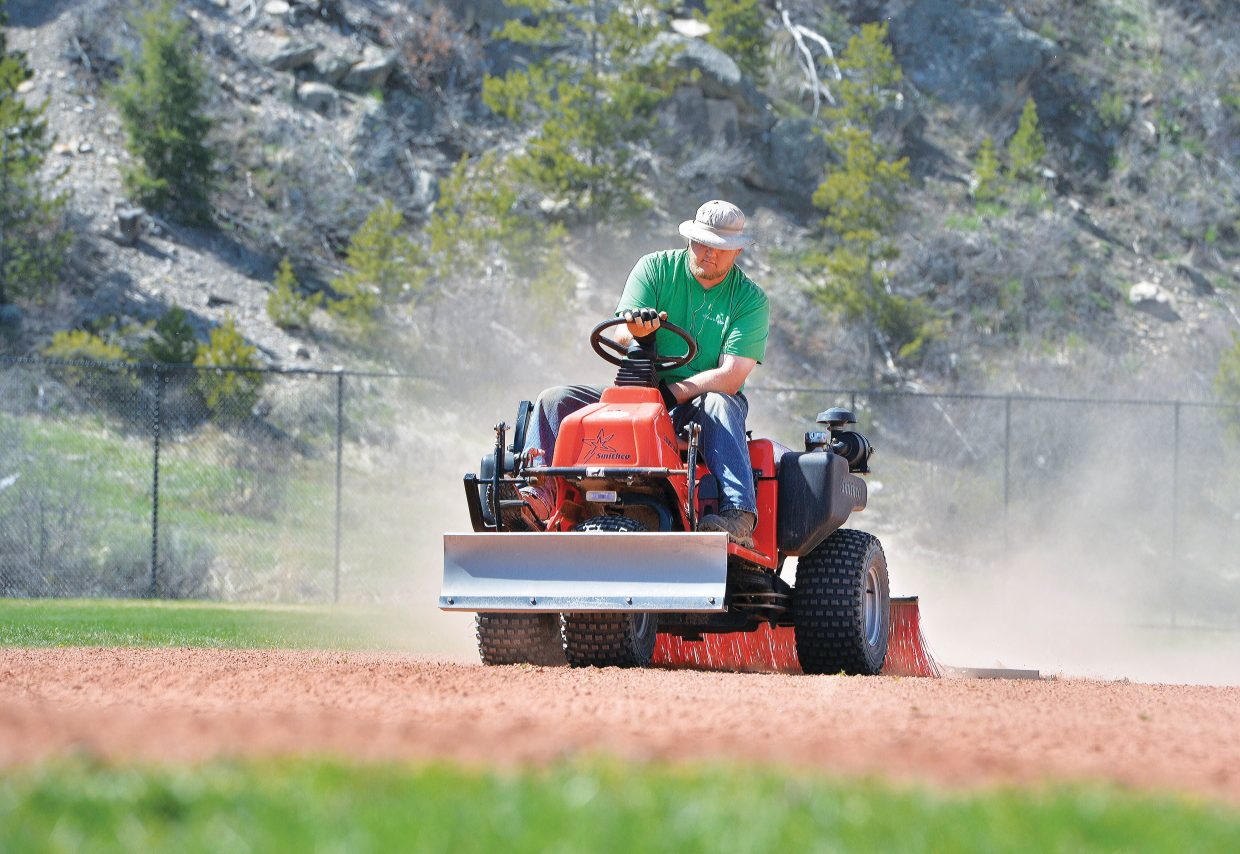 Steamboat Springs Parks and Community Services employee Jacob Girty rakes Simillion field in the spring. The city is currently working to put together a budget that would increase government expenditures by about $1.6 million next year.