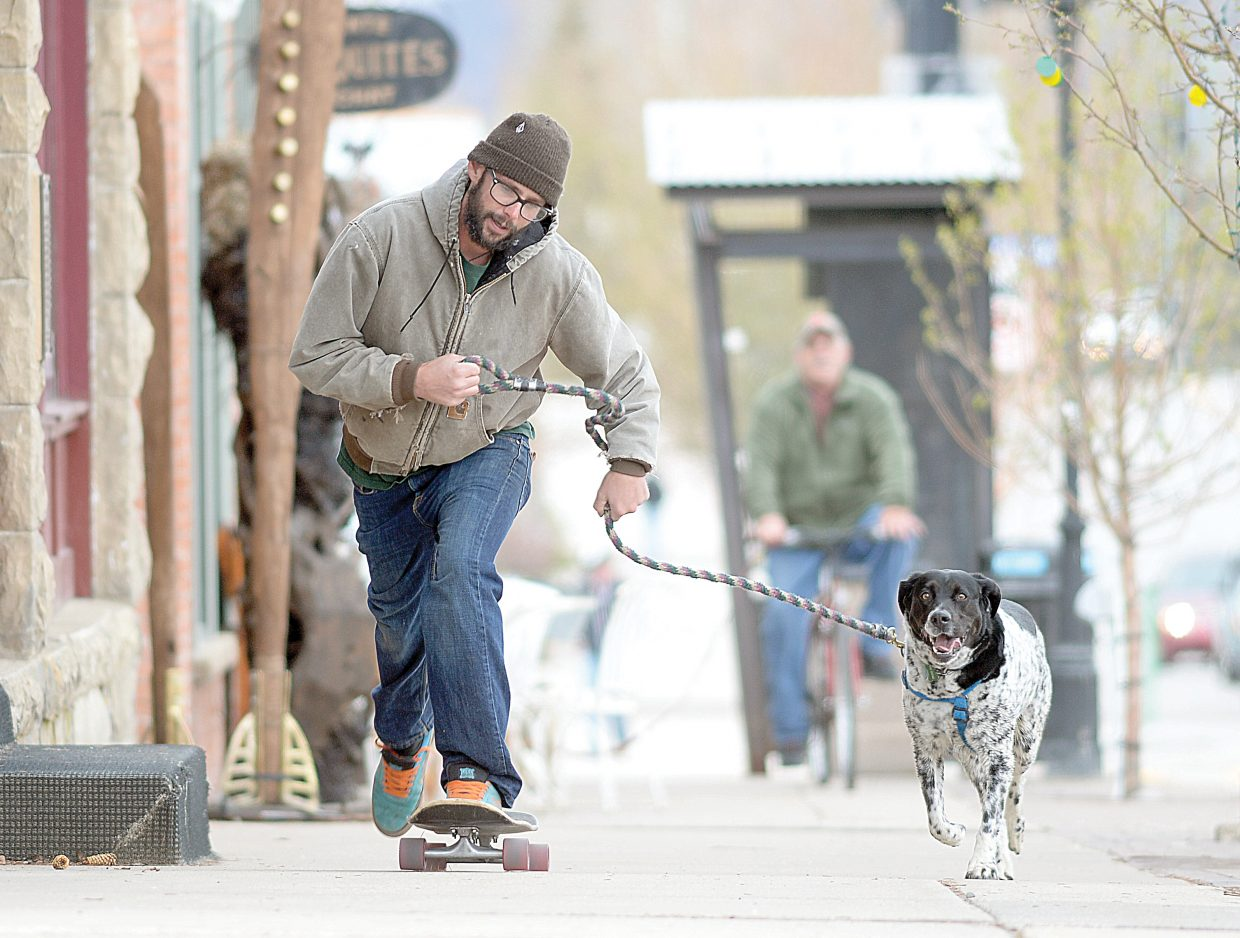 Justin Griffith and his dog, Buddy Good Times, roll along Lincoln Avenue on Tuesday afternoon in downtown Steamboat Springs.