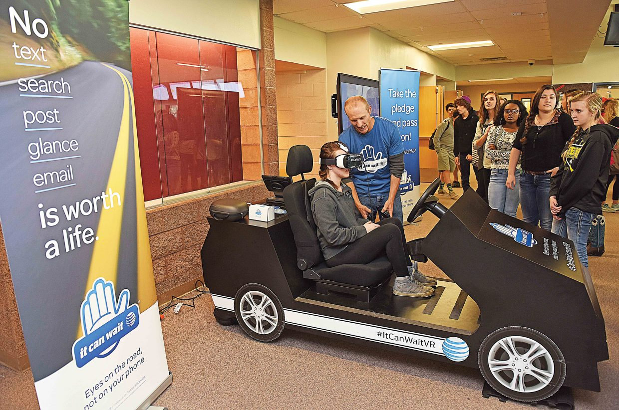 """Ryan Lucas, a teacher at Colorado Mountain College who was contracted to work with the """"It Can Wait"""" campaign, works with Steamboat Springs High School sophomore Ashlan Alicea as part of a distracted driving simulation that was set up in the common area of the school Friday afternoon. The simulator showed students the dangers of distracted driving and asked them to sign a pledge saying they would not text and drive."""
