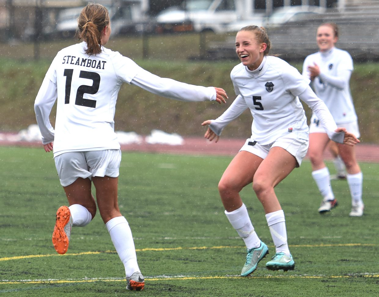 Brooke Buchanan, right, celebrates with Natalie Bohlmann after Bohlmann scored in the first half of Friday's game against Palisade.
