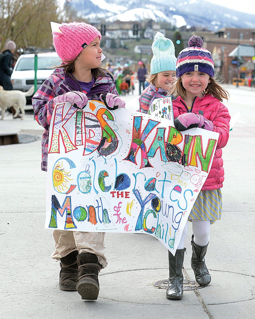 Nale Meek, left, and Gigi Lobeck carry the Kids Kabin banner down Lincoln Avenue on Wednesday morning as part of the annual Children's Parade. The parade was held as part of the Month of the Young Child celebration.