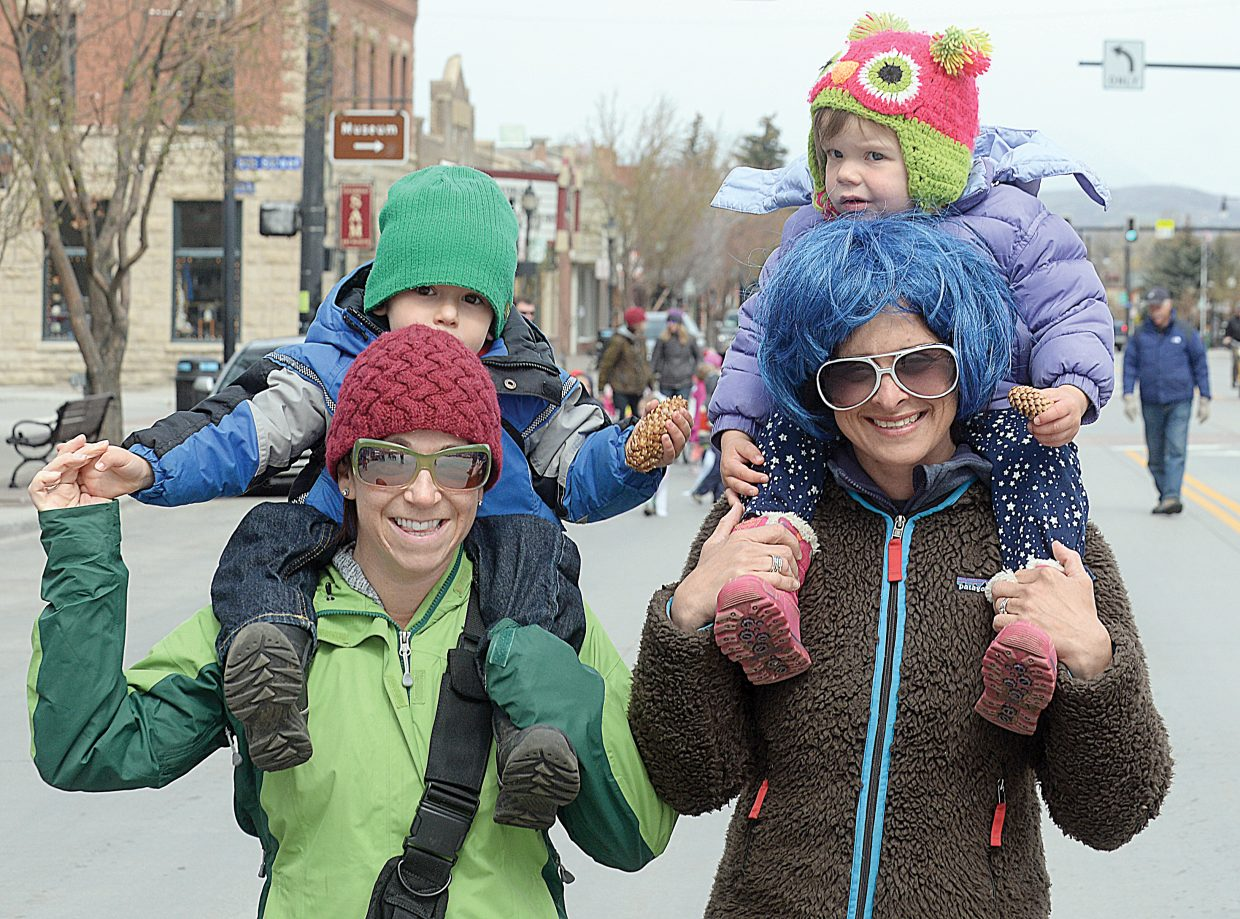 Wyatt, on mom Amy's back, and Brennan Phillips, on Jen Murphy's back, enjoyed getting up and down Lincoln Avenue with ease Wednesday morning during the annual Children's Parade. The event was part of the Month of the Young Child celebration.