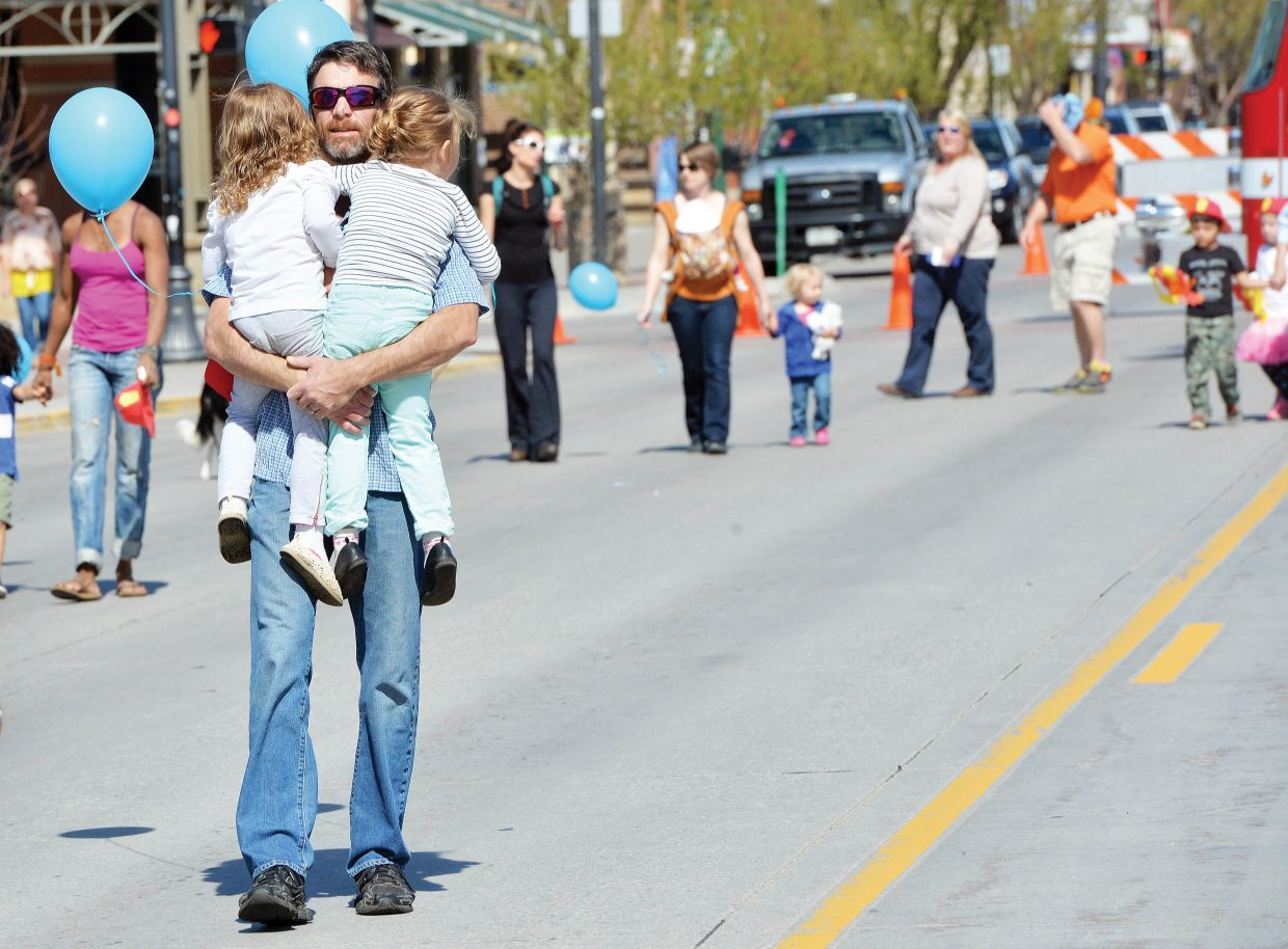 """Clay Gardner carries his 4-year-old twin daughters Lillian, left, and Sophia during the First Impressions Children's Parade. April was the """"Month of the Young Child,"""" and the annual parade was part of the celebration in Steamboat Springs."""