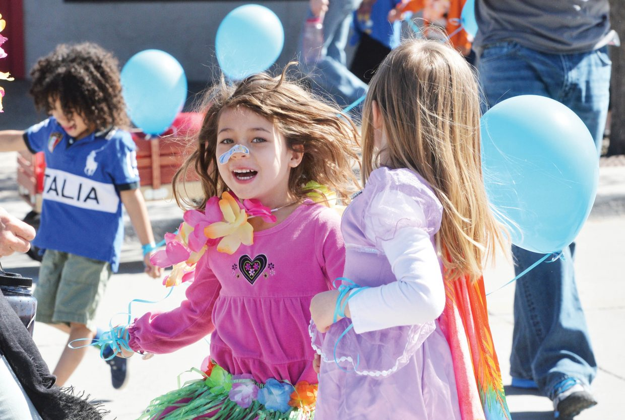 """Zoe Muir, left, and Vivian Sloop of Holy Name Preschool dance their way down Lincoln Avenue during the First Impressions Children's Parade. April was the """"Month of the Young Child"""" and the annual parade was part of the celebration in Steamboat Springs."""