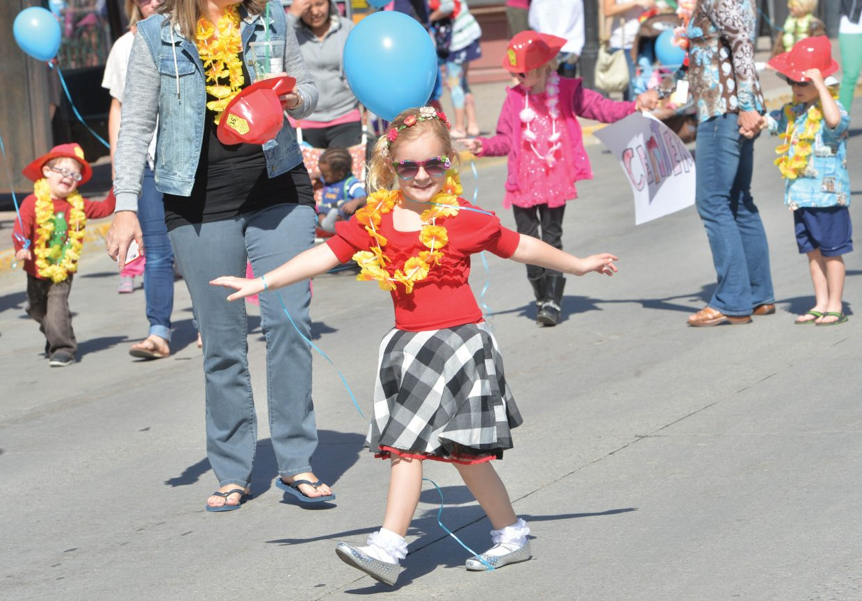 Harlo Adams dances in the street while taking part in the First Impressions Children's Parade Thursday morning.