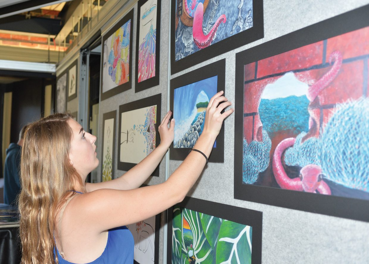 Art student Tanner Stover hangs her work for the Steamboat Springs AP art class exhibit.