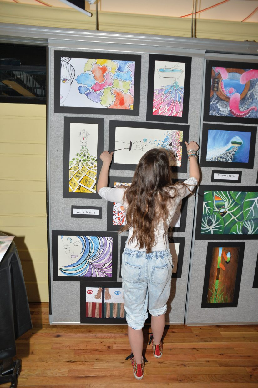 Art student Annie Martin hangs her work that will be displayed for the Steamboat Springs AP art class exhibit.