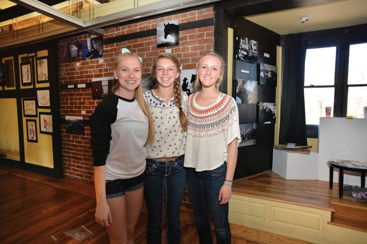 Art students, from left, Keala Fraioli, Hallie Myhre and Kady Look hang out while hanging the Steamboat Springs AP art class exhibit.