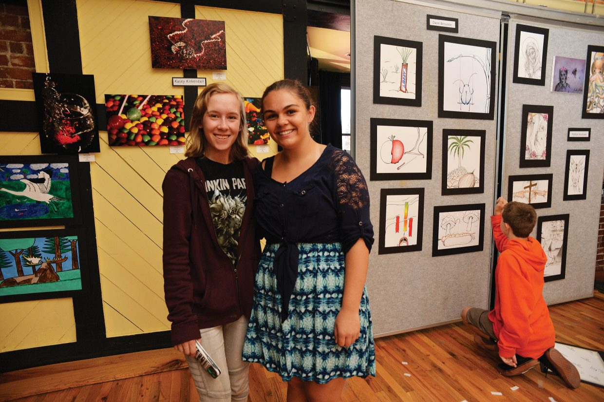 Arts students Kasey Kirkendall, left, and Joylynn Phillips hang their work for the Steamboat Springs AP art class exhibit.
