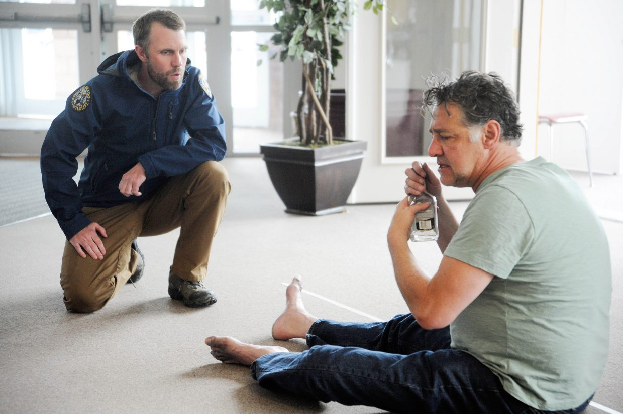 Stagecoach State Park Senior Ranger Andrew Dean tries to help a homeless man, portrayed by professional actor Thomas Borrillo, during crisis intervention training last week at Steamboat Springs High School.