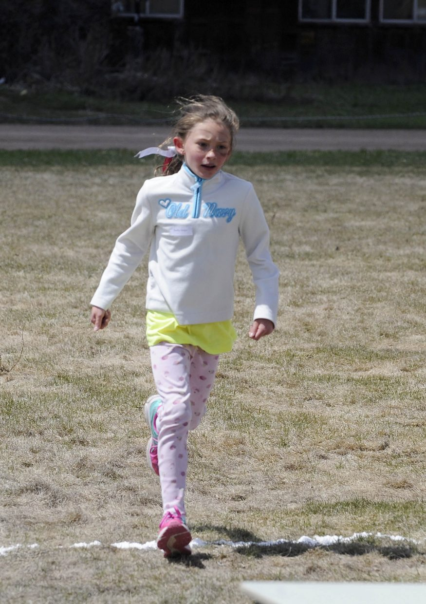The first girl to finish, third grader Shelby Geiger, crosses the finish line.