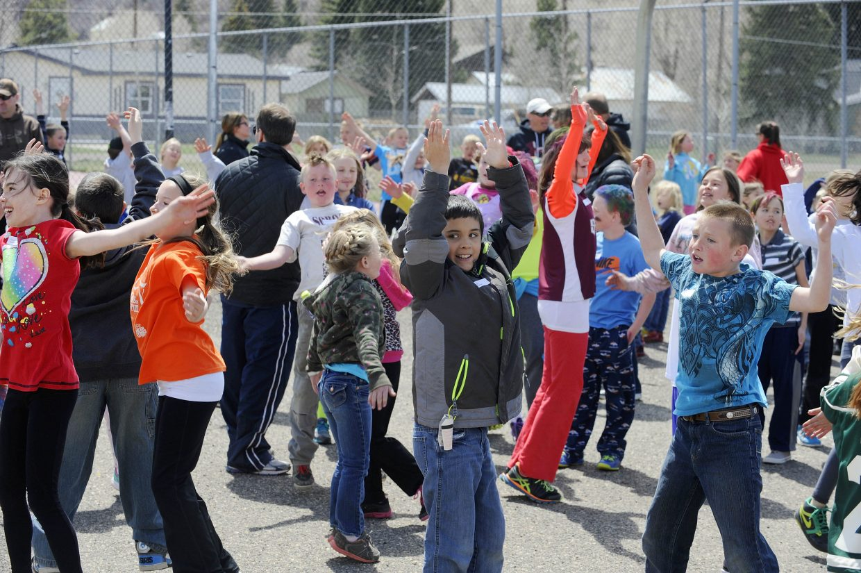 Students do jumping jacks before starting the mile-long run at the school.