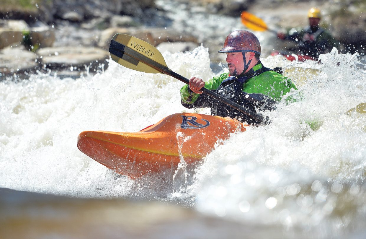 Kayaker Sage McDermott plays in the white water of the Yampa River Friday afternoon. The river flow is on the rise as snow continues to melt from valleys and peaks surrounding Steamboat Springs.