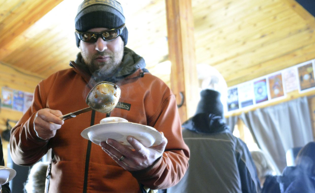 Derek Leidigh scoops a ladle of Bison Bacon Chipotle Chili during the 2014 Great North Routt Chili Cook Off.