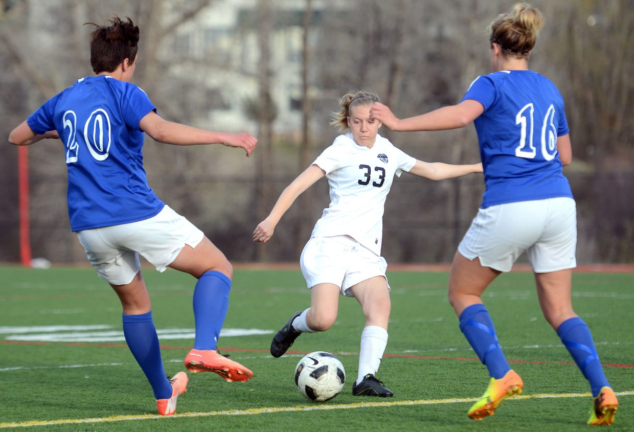 Steamboat's Colleen Garrecht-Connelly tries to move the ball as a pair of Fruita defender collapse on her.