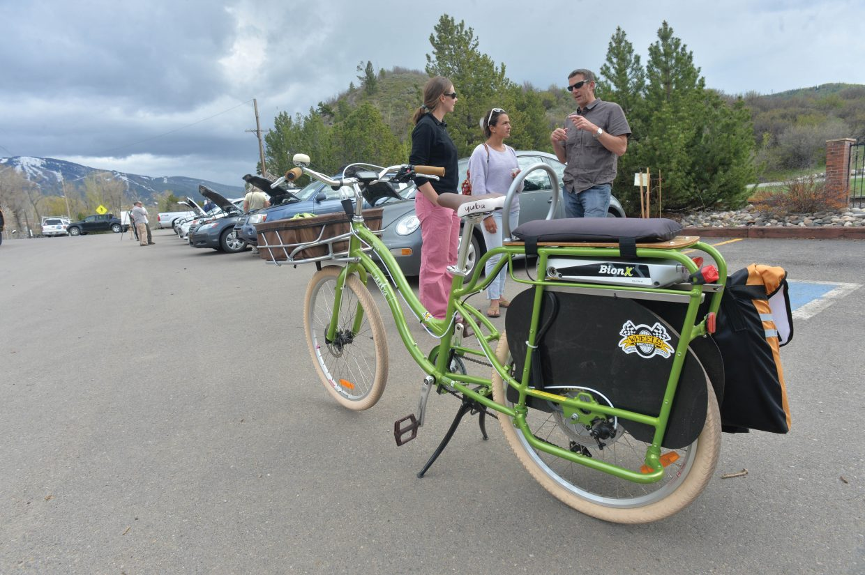 Gina Wither, far right, talks to Emily Colin, middle, and Paul Ralston, left, about her Yuba electric bike during the Alternative Fuels and Gas Saving Technology Expo Tuesday afternoon in the parking lot of the Depot Art Center. The show featured a number of different alternative and fuel saving vehicles, and their owners who were on hand to awnser questions.