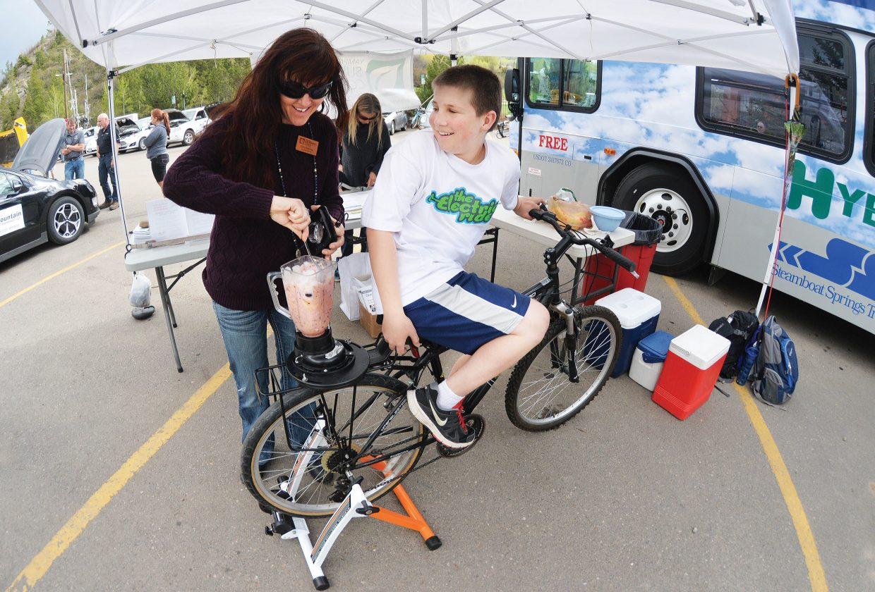Spencer Romig, on bike, and Andy Kennedy make smoothies using a bike-powered blender at Alternative Fuels and Gas Saving Technology Expo Tuesday afternoon at the Depot Art Center.