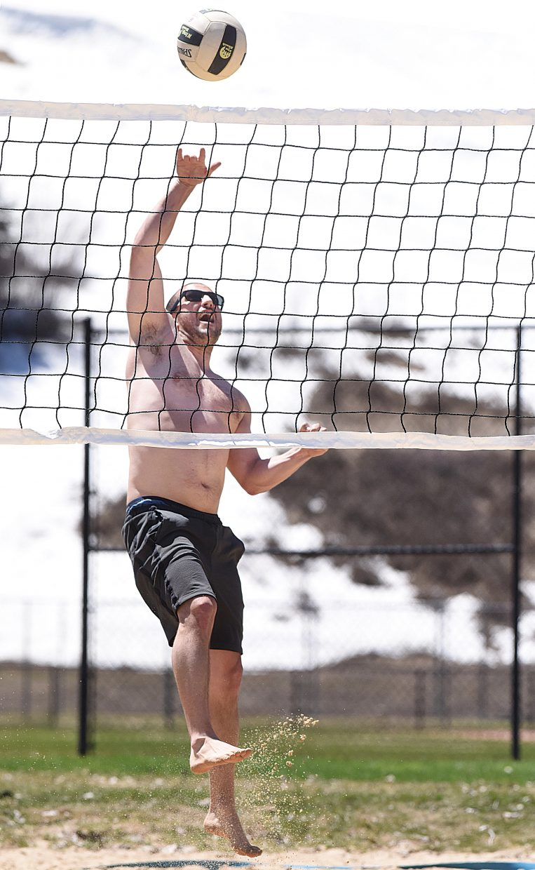 Beau Bell spikes the ball over the net while playing volleyball with friends at Howelsen Hill. Bell and his friends were more than happy to enjoy Wednesday's warm weather as the snow on slopes of Howelsen Hill, which can be seen in the background, continued to melt.