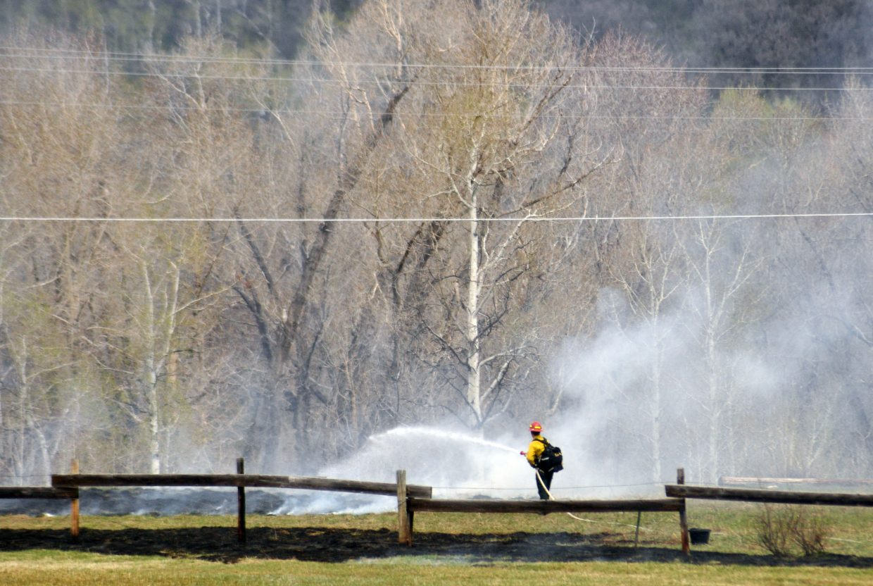 A Steamboat Springs Fire Rescue firefighter works to put out a wildfire Monday morning in Strawberry Park.