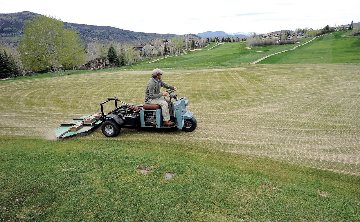 Jesse Novak uses a small tractor to top dress the greens at the Rollingstone Ranch Golf Club. The course is scheduled to open Friday, and the Haymaker Golf Course plans to open Saturday as the golfing season shifts into high gear in Steamboat Springs this week.