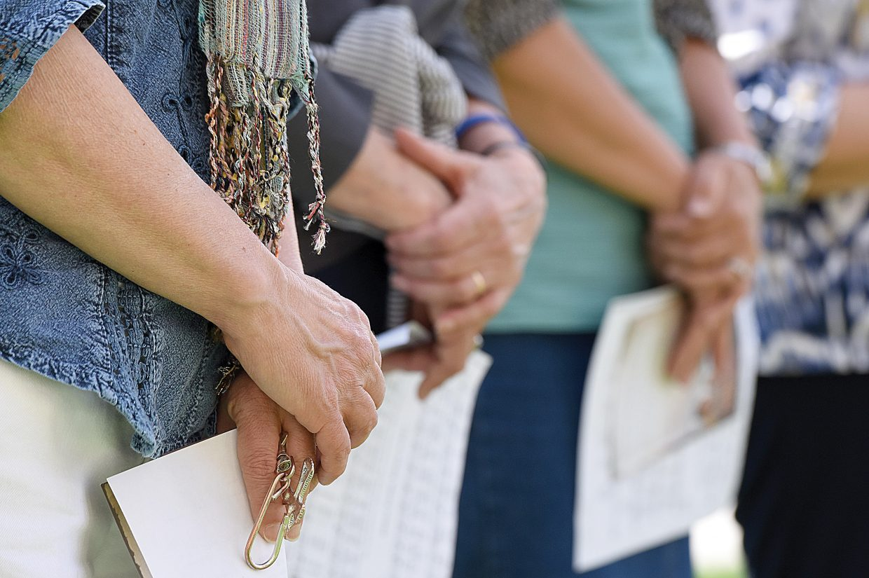 People stand with their hands clasped while listening to others pray on the courthouse lawn Thursday as part of the National Day of Prayer.