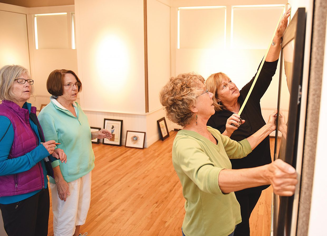 Cindy Wither holds a watercolor painting as Cher Dooley uses a tape measure to center the piece on the wall of the Depot Arts Center earlier this week. The watercolor can be viewed at the Steamboat Springs First Friday Opening from 5 to 8 p.m. May 6 or at a more intimate gathering with the artists during Artist Happy Hour at 5:30 p.m. May 10.