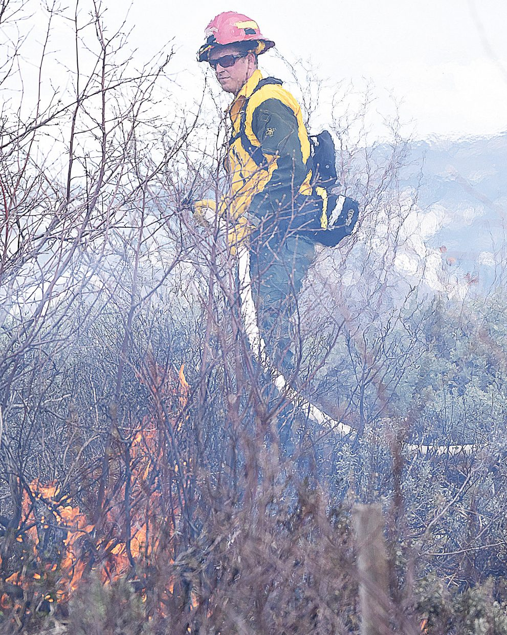 Nick Kuchulis, with Steamboat Springs Fire Rescue, cleans up some hot spots after a controlled burn got out of control on Thorpe Mountain Thursday afternoon. Crews from Steamboat Springs and Oak Creek arrived in time to knock the fire down before it became a threat to several nearby homes in the area.
