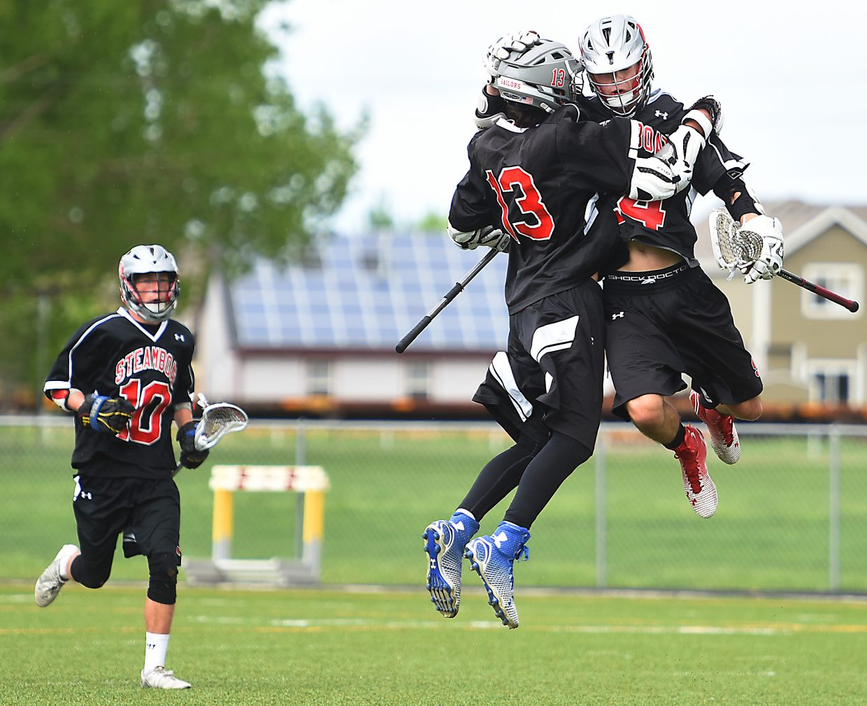 Willy Gunn, left, and Drew Williamson celebrate a goal Wednesday during the lacrosse state playoffs in Windsor.
