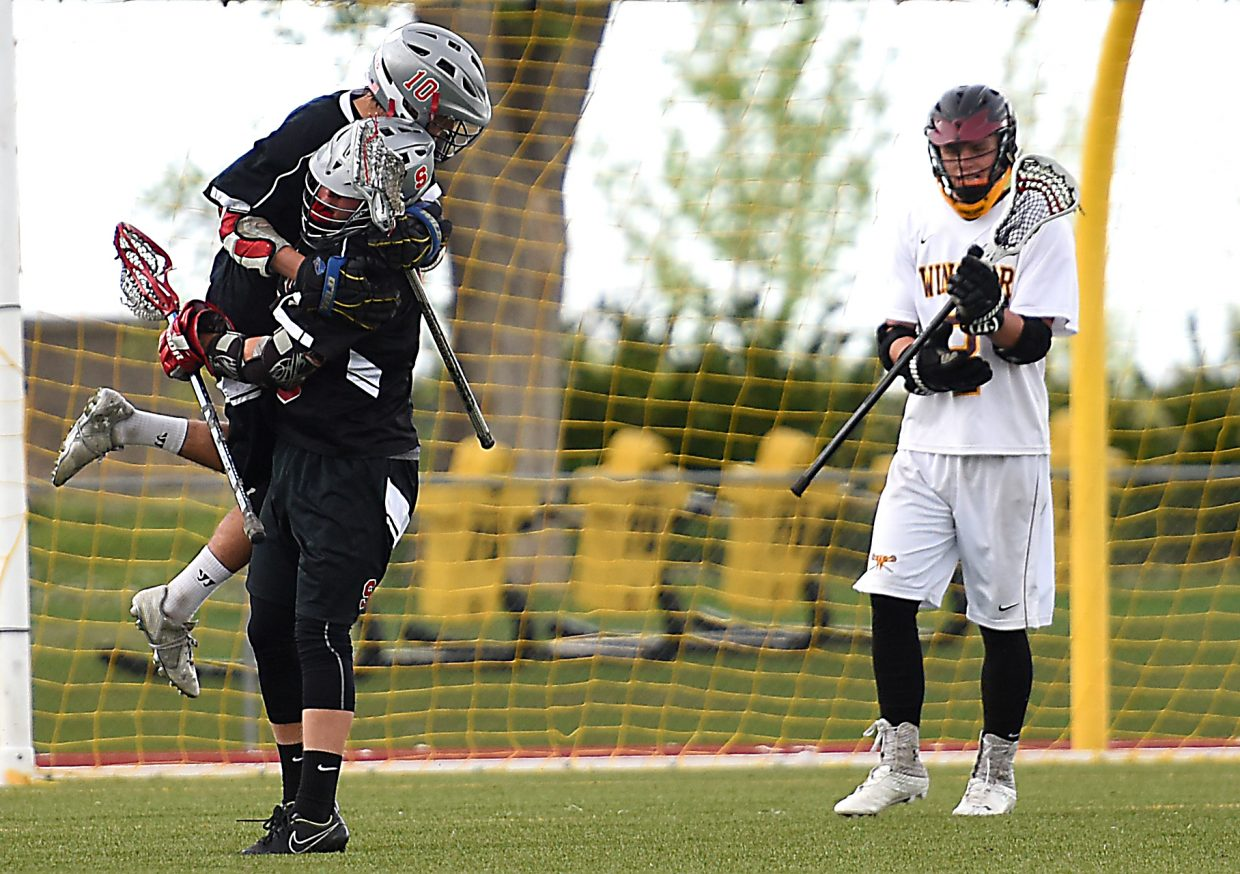 Jackson Draper, left, and Will Petersen celebrate a goal Wednesday in the lacrosse state playoffs.