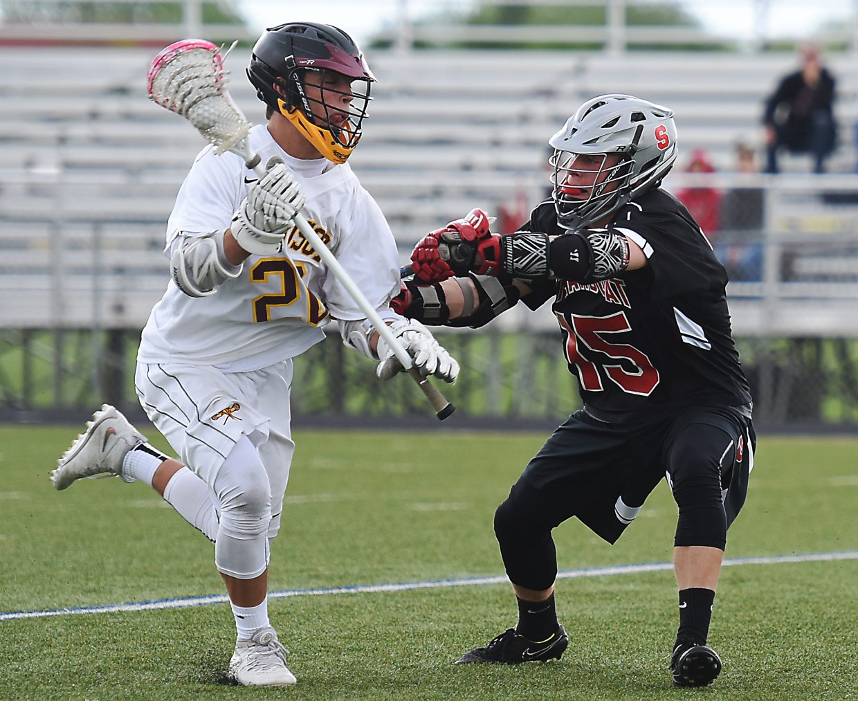 Steamboat's Will Petersen checks his opponent Wednesday during the state lacrosse playoffs.