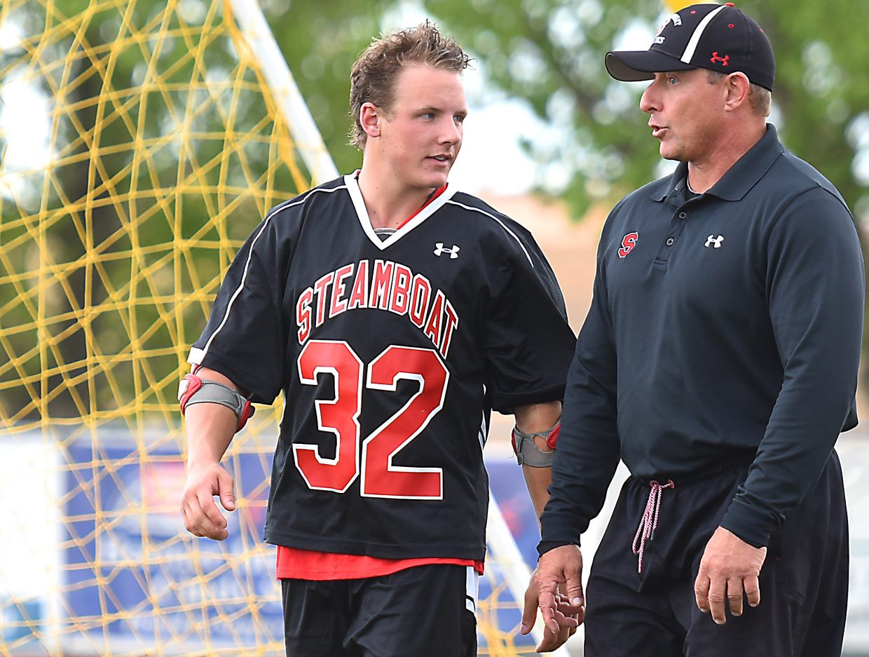 Steamboat senior Mitch McCannon and his father, Mike McCannon, talk about Wednesday's lacrosse playoff game during halftime.