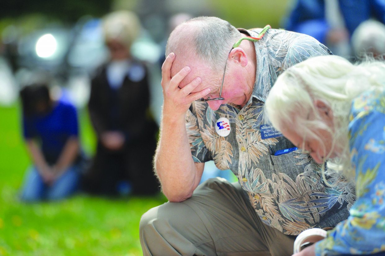 Steamboat Springs resident Scott Ford takes a knee to pray while taking part in the National Day of Prayer on the Routt County Courthouse lawn in Steamboat Springs Thursday. Events recognizing The National Day of Prayer take place in cities across the United States on the first Thursday of May.