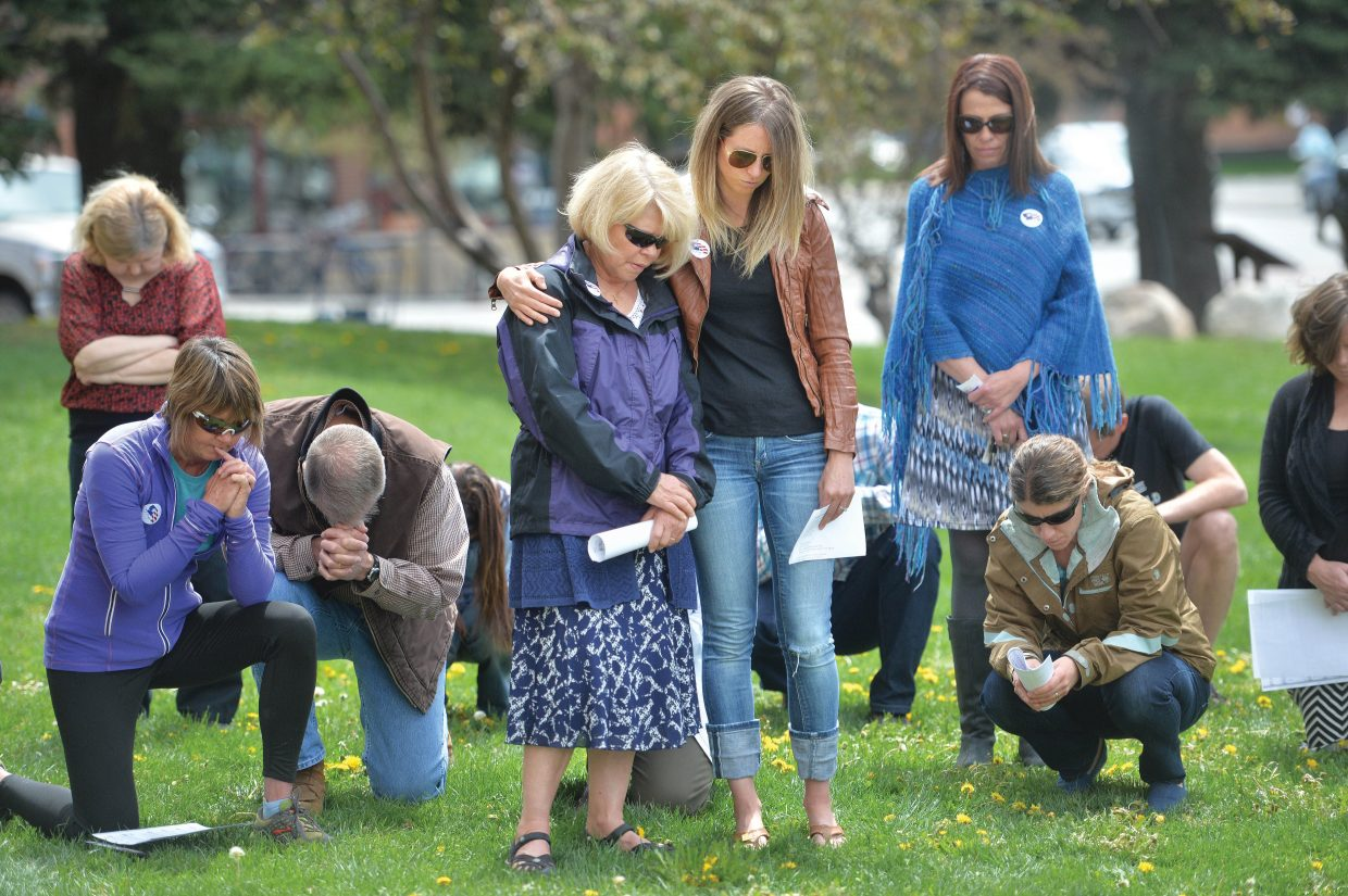 Bonnie Baggenstoss, left, and Kel Elwood take listen as Del Lockhart prays during the National Day of Prayer on the Routt County Courthouse lawn in Steamboat Springs Thursday. Events recognizing The National Day of Prayer take place in cities across the United States on the first Thursday of May.