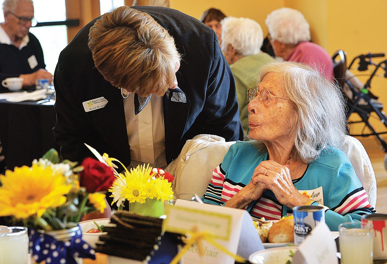 Alice Klauzer, who is on the board of directors for the Routt County Council on Aging, delivers flowers to 103-year-old Anna Wichern during the Spring Fling at the Community Center on Friday at noon. The event was a special recognition for seniors, which included lunch served by students from the Emerald Mountain School, entertainment by Yampa Valley Boys and lunch.