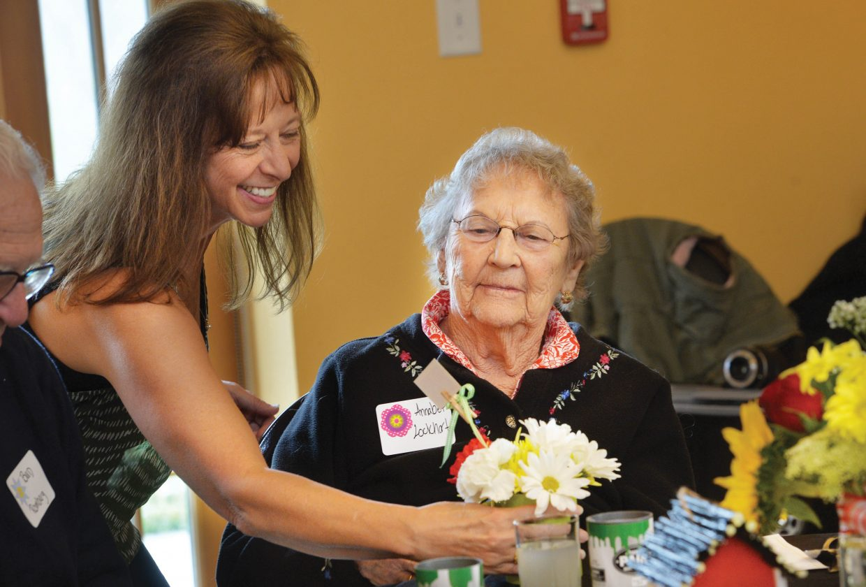 Pegi Semmerman, who is on the board of directors for the Routt County Council on Aging, delivers flowers to Annabeth Lockhart during the Spring Fling at the Community Center on Friday at noon. The event was a special recognition for seniors, which included lunch served by students from the Emerald Mountain School, entertainment by Yampa Valley Boys and lunch.