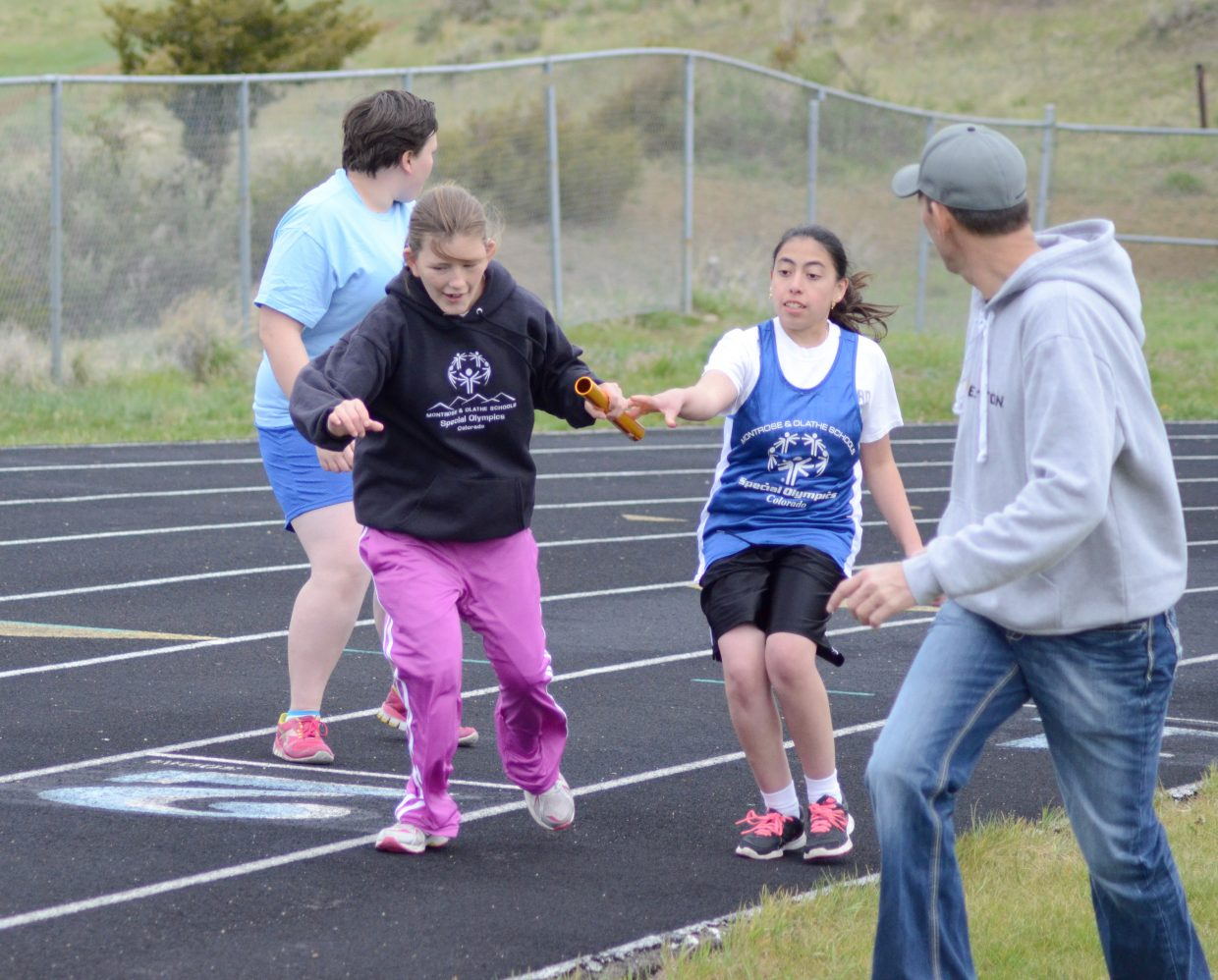 Carolina Jaramillo hands off the baton to teammate Clarissa Hardy in the four by 100-meter relay at the Western Area Summer Games Saturday.