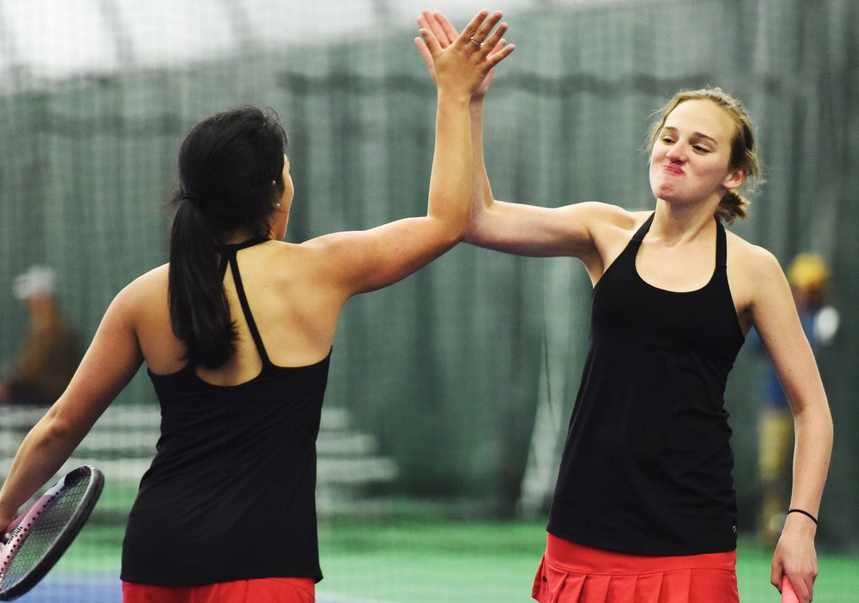 Shea Burger, right, and Norma Techarukpong share a high five during a match earlier this season at Vail Mountain. Burger and Techarukpong are among nearly a dozen Sailors who will begin competition this week in the Class 4A state tennis tournament in Pueblo.