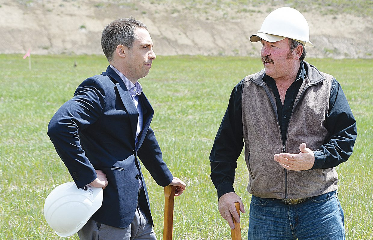 Routt County Commissioner Doug Monger, who also serves as Yampa Valley Affordable Housing Authority board president, talks with Michael Rossi of Enterprise Community Investment, Inc., the asset manager for American Express, the major investor in The Reserves at Steamboat affordable housing development, during a groundbreaking ceremony Wednesday. The new affordable housing development is being built just off of Routt County Road 129 near the intersection with U.S. Highway 40.