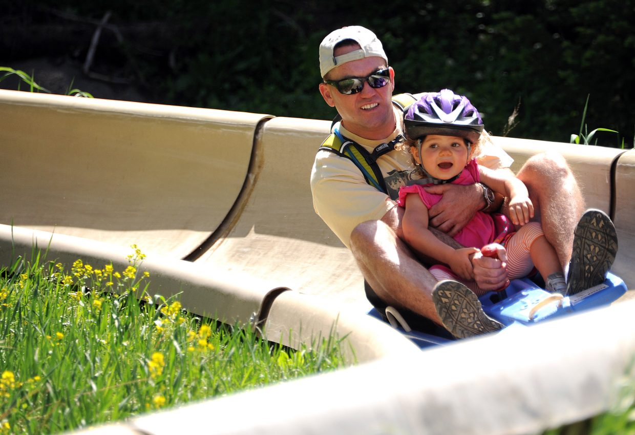 Dwain Carnes and Peyton, 2, fly down the Alpine Slide on Howelsen Hill in Steamboat Springs in a past summer.