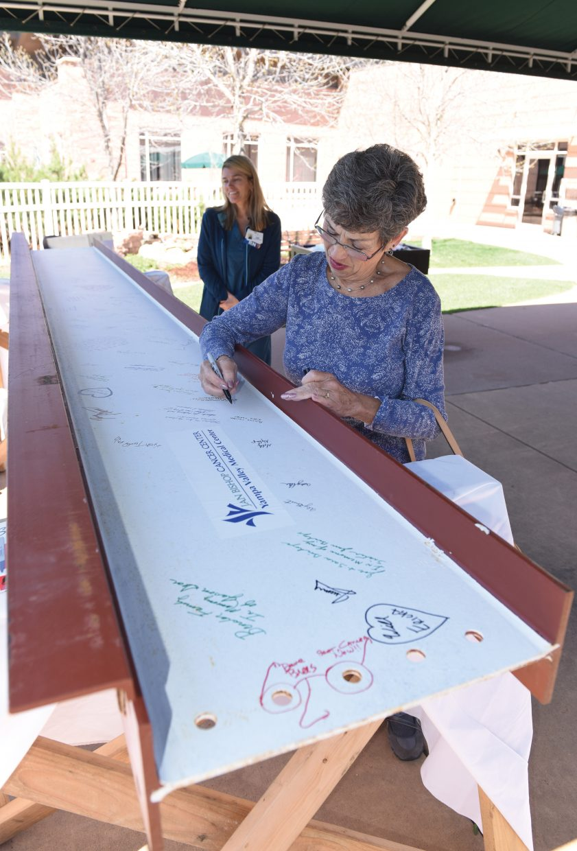 Longtime Yampa Valley Medical Center volunteer Ramona Carlton signs a steel beam during an employee barbecue Thursday afternoon. The beam, which was signed by staff, volunteers, physicians and cancer survivors, will be placed in the new Jan Bishop Cancer Center during a topping out ceremony May 18.